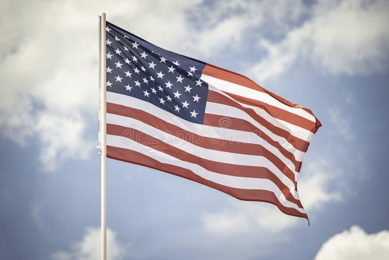 Bandiera americana su un cielo blu con le nuvole immagine stock