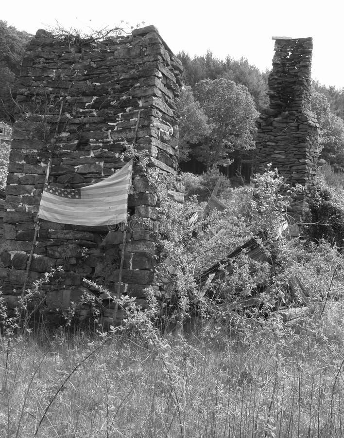 Bandiera americana su un vecchio camino di pietra di vecchia fattoria abbandonata immagini stock libere da diritti