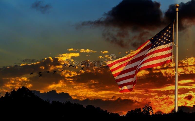 Bandiera americana sull'asta della bandiera che ondeggia nella bandiera americana del vento davanti al cielo luminoso fotografia stock