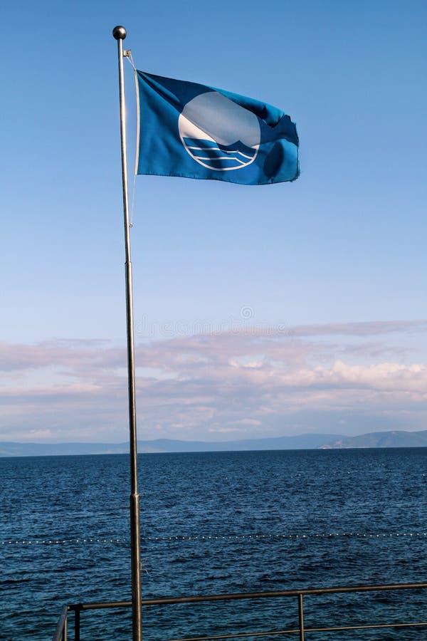 Bandiera blu per il volo pulito della bandiera del premio di qualità della spiaggia, che il mezzo ha raggiunto le norme specifich fotografie stock libere da diritti