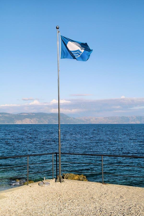 Bandiera blu per il volo pulito della bandiera del premio di qualità della spiaggia, che il mezzo ha raggiunto le norme specifich immagine stock libera da diritti