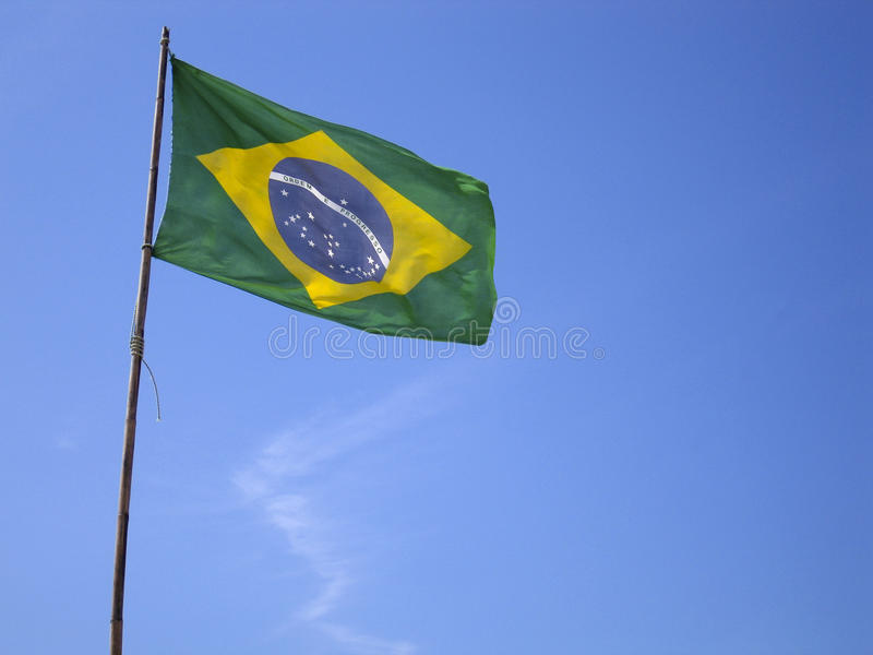 Bandiera brasiliana su cielo blu immagine stock