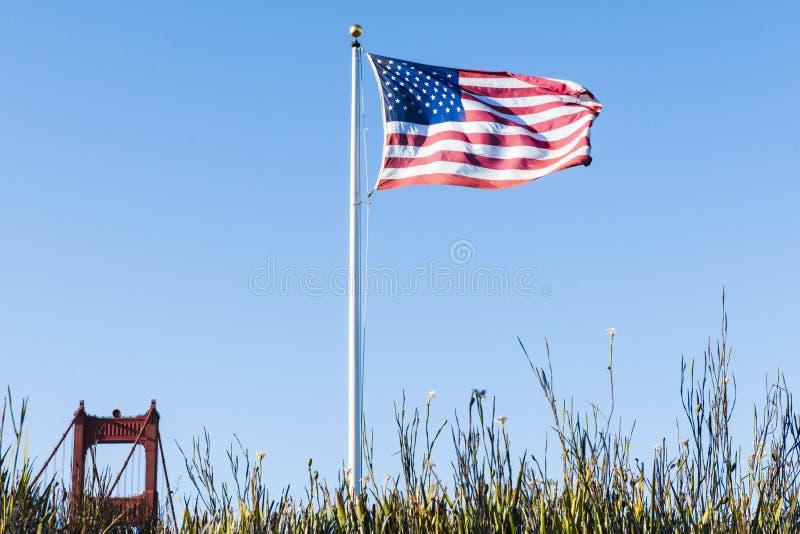Bandiera degli Stati Uniti e una cima un golden gate bridge Sa della torre fotografia stock libera da diritti
