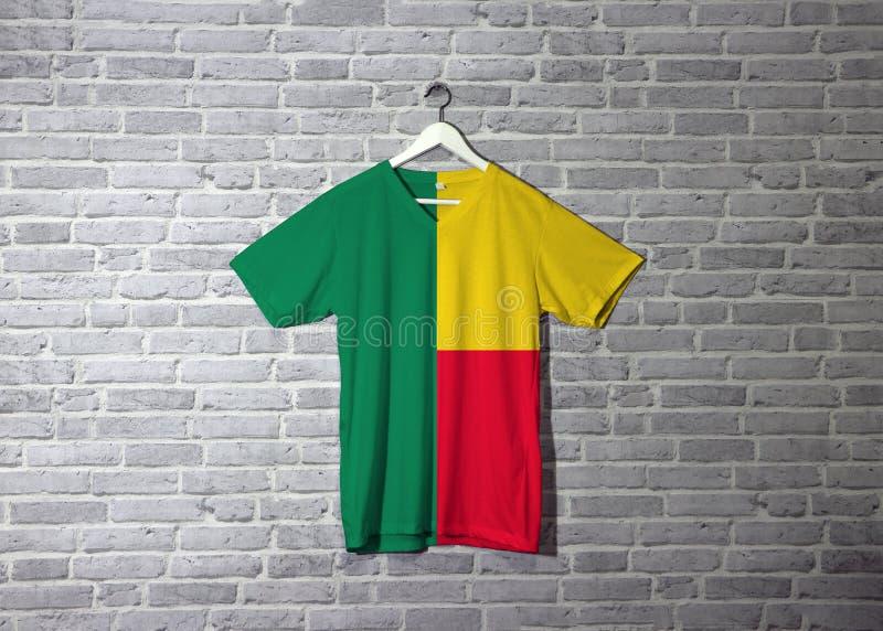 Bandiera del Benin sulla camicia ed appendere sulla parete con la carta da parati del modello del mattone illustrazione di stock