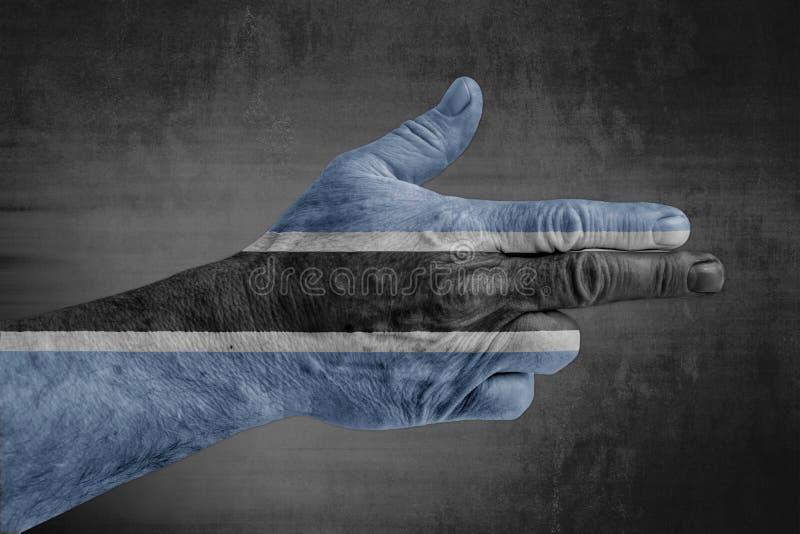 Bandiera del Botswana dipinta sulla mano maschio come una pistola immagine stock