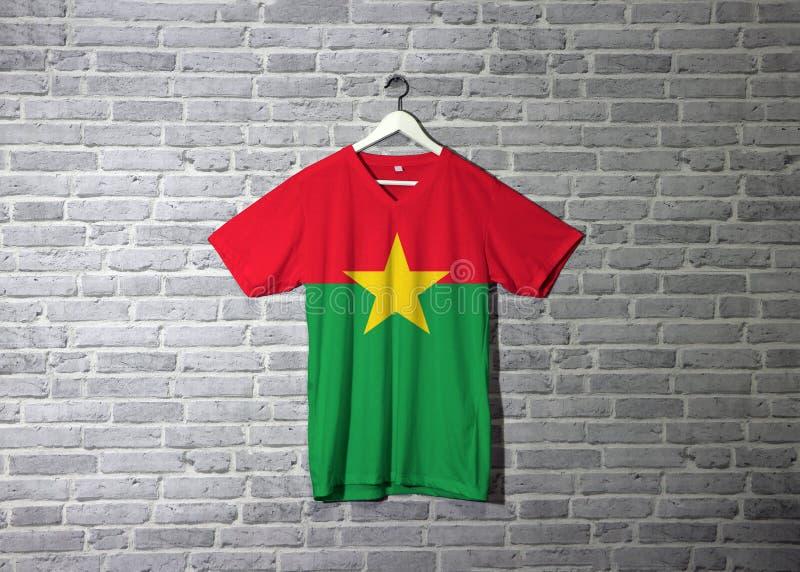 Bandiera del Burkina Faso sulla camicia ed appendere sulla parete con la carta da parati del modello del mattone illustrazione vettoriale