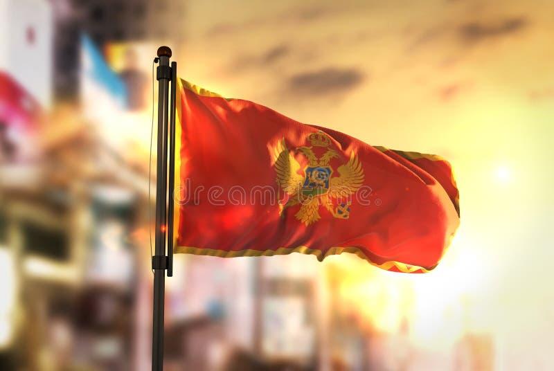 Bandiera del Montenegro contro fondo vago città ad alba Backl fotografia stock libera da diritti