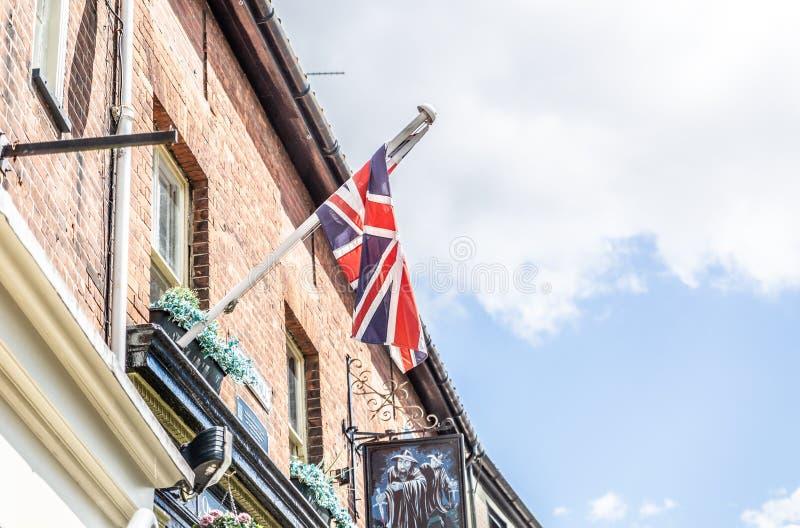 Bandiera del Regno Unito appesa a una facciata di mattoni di un tipico edificio inglese fotografia stock libera da diritti