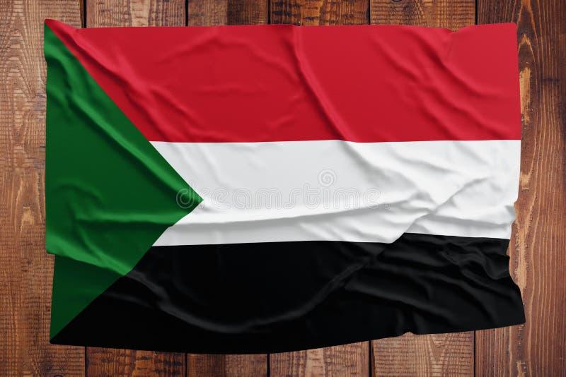 Bandiera del Sudan su un fondo di legno della tavola Vista superiore corrugata della bandiera sudanese fotografie stock