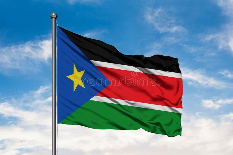 Bandiera del Sudan del sud che ondeggia nel vento contro il cielo blu nuvoloso bianco immagini stock