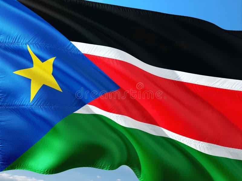 Bandiera del Sudan del sud che ondeggia nel vento contro il cielo blu profondo Tessuto di alta qualit? immagine stock