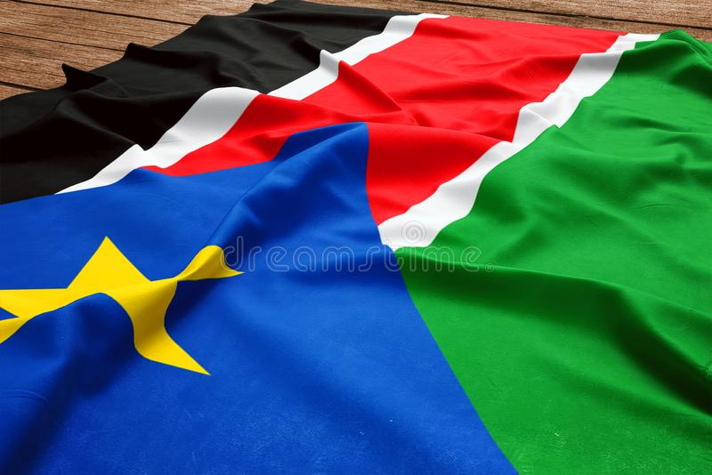 Bandiera del Sudan del sud su un fondo di legno dello scrittorio Vista superiore della bandiera di seta fotografia stock