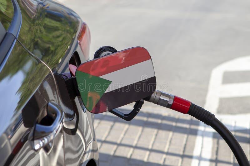 Bandiera del Sudan sulla falda del riempitore del combustibile del ` s dell'automobile fotografia stock