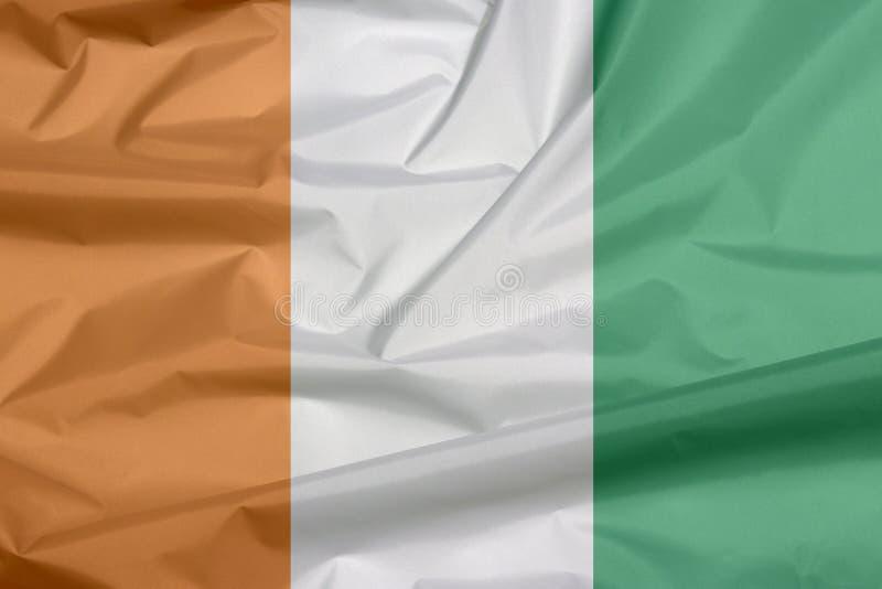 Bandiera del tessuto della piega di Costa d'Avorio del fondo della bandiera di Costa d'Avorio royalty illustrazione gratis