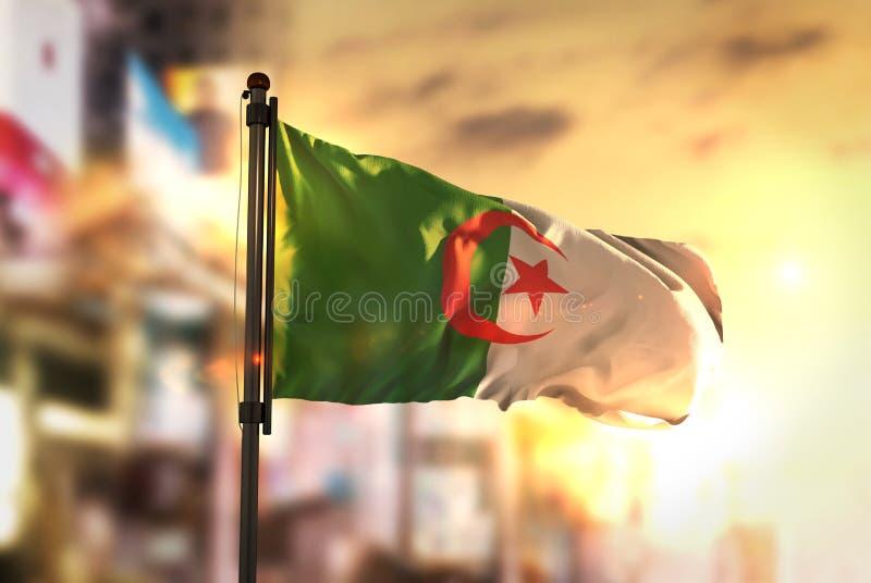 Bandiera dell'Algeria contro fondo vago città ad alba Backligh fotografia stock