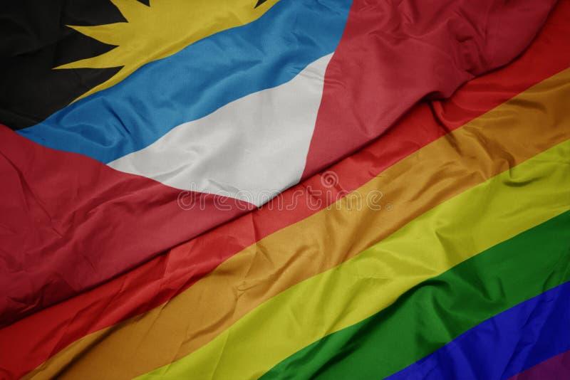 bandiera dell'arcobaleno e bandiera nazionale gay variopinte d'ondeggiamento dell'Antigua e di Barbuda immagine stock libera da diritti