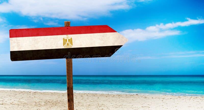 Bandiera dell'Egitto sul segno di legno della tavola sul fondo della spiaggia È segno dell'estate dell'Egitto illustrazione vettoriale