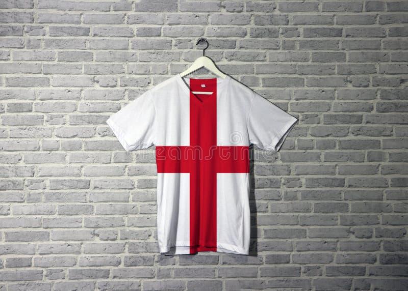 Bandiera dell'Inghilterra sulla camicia ed appendere sulla parete con la carta da parati del modello del mattone illustrazione vettoriale