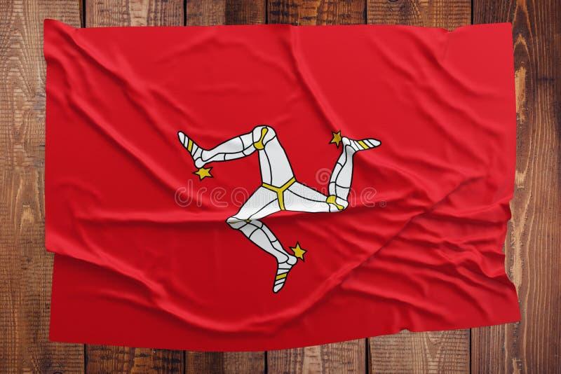 Bandiera dell'Isola di Man su un fondo di legno della tavola Vista superiore corrugata della bandiera fotografia stock libera da diritti