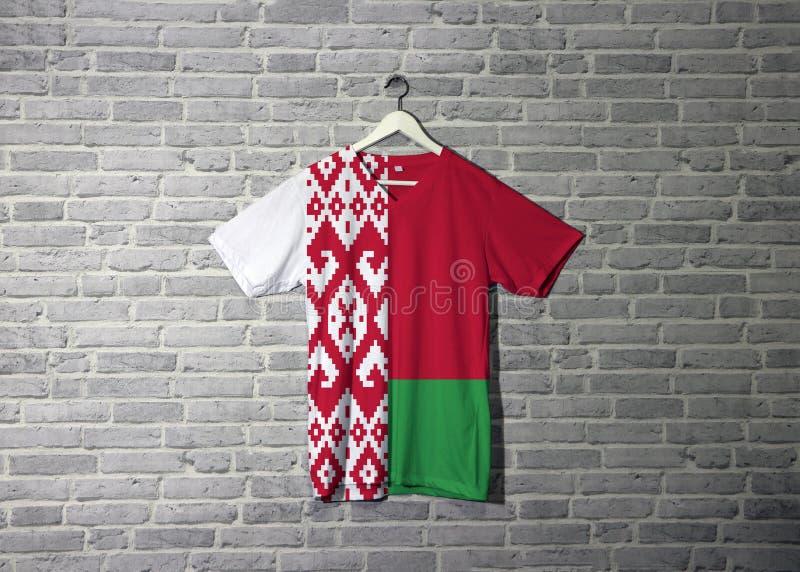 Bandiera della Bielorussia sulla camicia ed appendere sulla parete con la carta da parati del modello del mattone illustrazione vettoriale