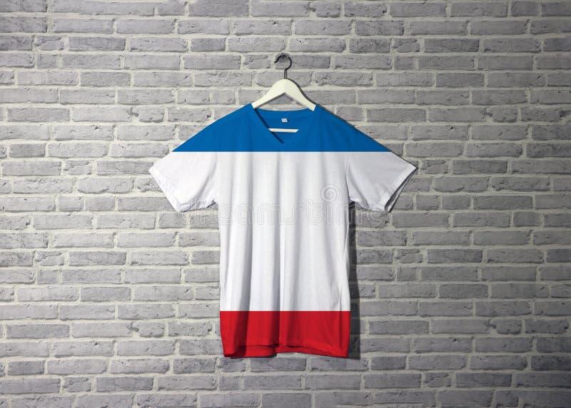 Bandiera della Crimea sulla camicia ed appendere sulla parete con la carta da parati del modello del mattone royalty illustrazione gratis