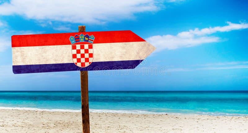 Bandiera della Croazia sul segno di legno della tavola sul fondo della spiaggia È segno dell'estate della Croazia illustrazione vettoriale