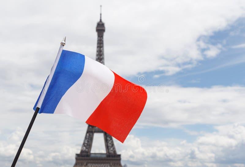 Bandiera della Francia contro la torre Eiffel fotografia stock