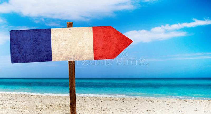 Bandiera della Francia sul segno di legno della tavola sul fondo della spiaggia È segno dell'estate della Francia illustrazione di stock