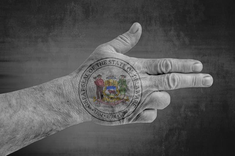 Bandiera della guarnizione del Delaware dello stato USA dipinta sulla mano maschio come una pistola illustrazione vettoriale