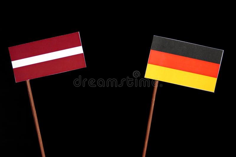 Bandiera della Lettonia con la bandiera tedesca sul nero fotografia stock