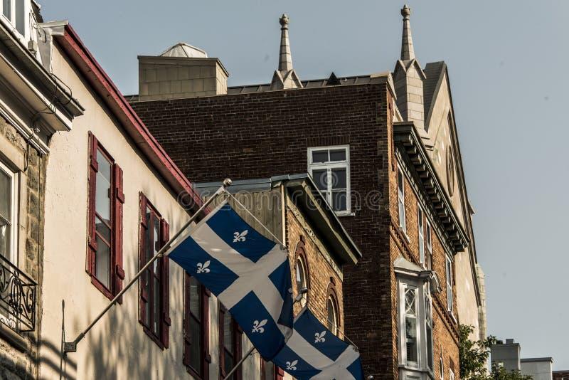 Bandiera della Quebec davanti ad una vecchia casa di più vecchia parte di Québec nella città più bassa - ville del basse fotografia stock libera da diritti