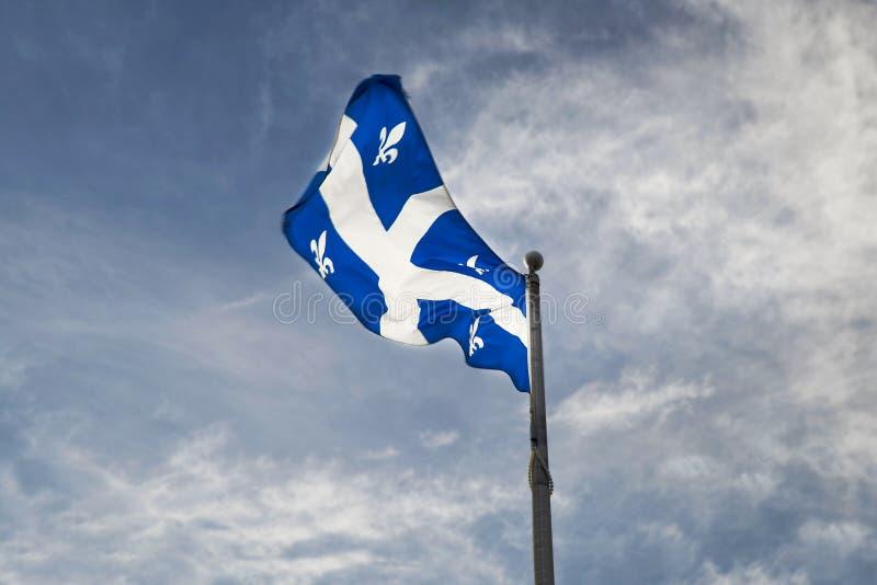 Bandiera della Quebec sull'asta della bandiera contro il cielo blu fotografie stock
