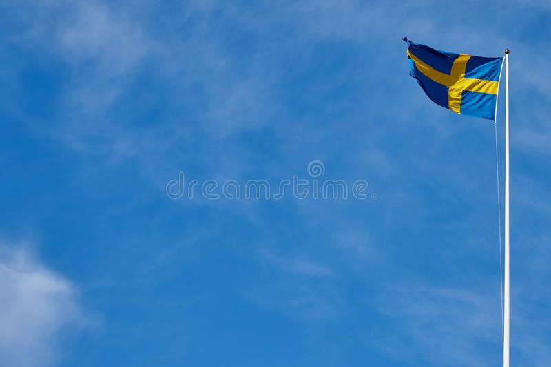 Bandiera della Svezia contro un cielo nuvoloso blu immagine stock