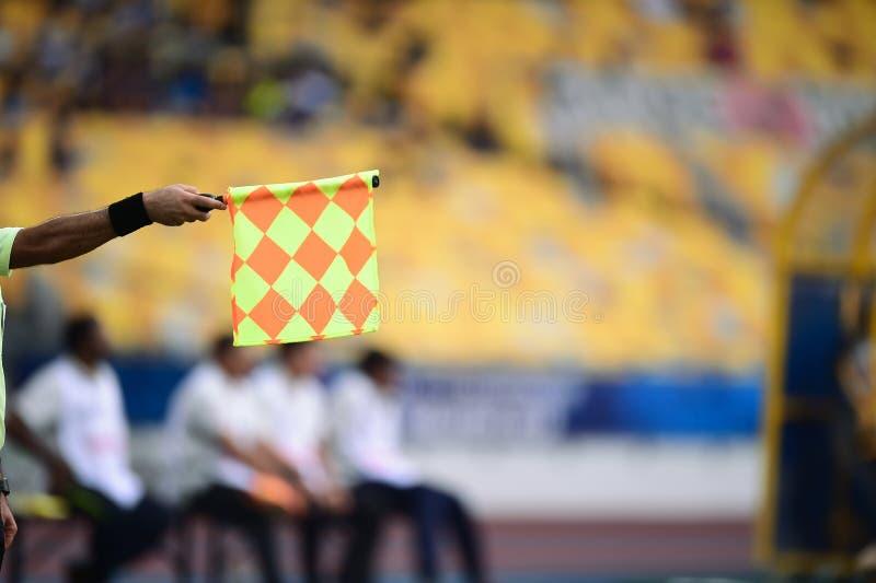 Bandiera della tenuta dell'assistente arbitro, segnale fuorigioco fotografia stock
