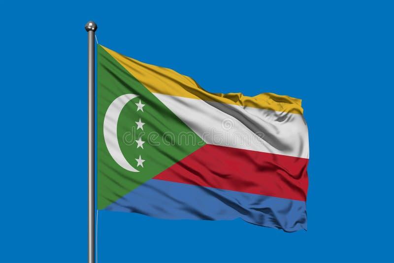 Bandiera delle Comore che ondeggiano nel vento contro il cielo blu profondo illustrazione di stock