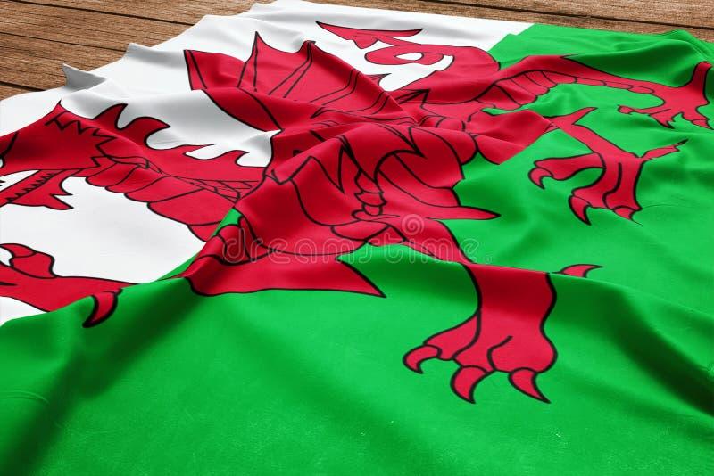 Bandiera di Galles su un fondo di legno dello scrittorio Vista superiore della bandiera di seta di Lingua gallese illustrazione di stock