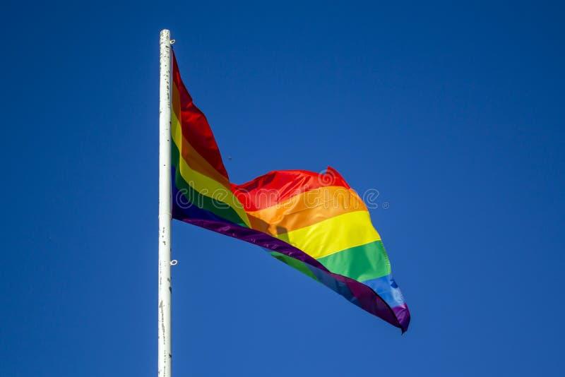 Bandiera di orgoglio dell'arcobaleno di LGBT contro cielo blu fotografie stock libere da diritti