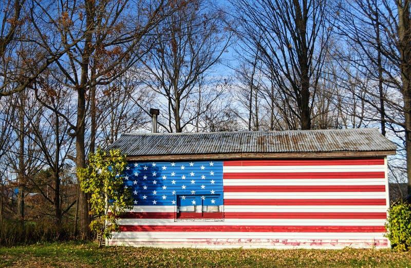 Bandiera di stelle e strisce dipinta su una casa americana rurale fotografie stock libere da diritti