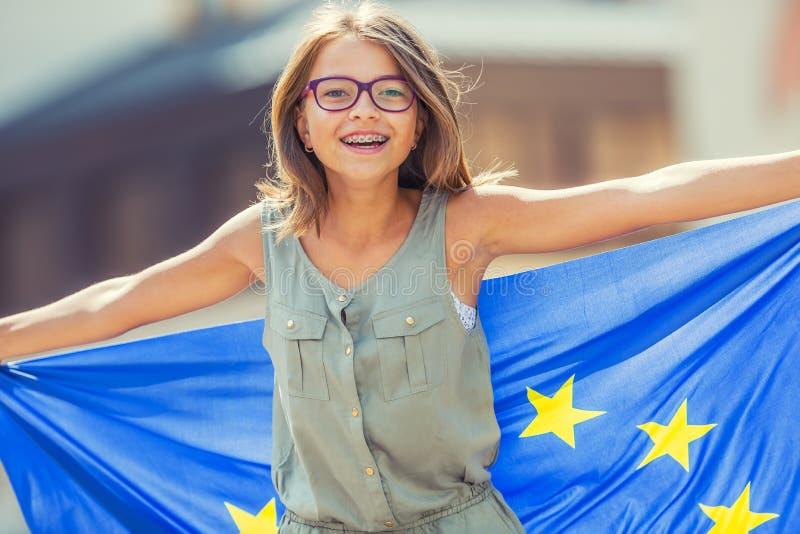 Bandiera di UE Ragazza felice sveglia con la bandiera dell'Unione Europea Giovane adolescente che ondeggia con la bandiera di Uni immagini stock libere da diritti