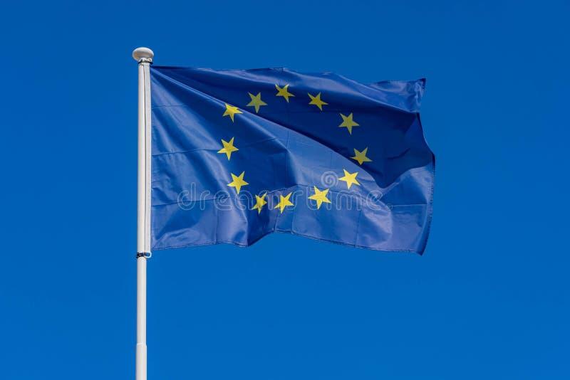 Bandiera di Unione Europea che soffia in vento in chiaro cielo blu anteriore immagine stock