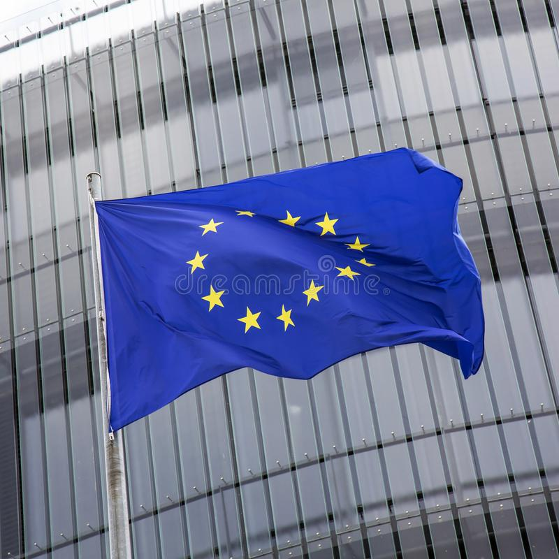 Bandiera di Unione Europea contro le finestre di costruzione moderna immagini stock