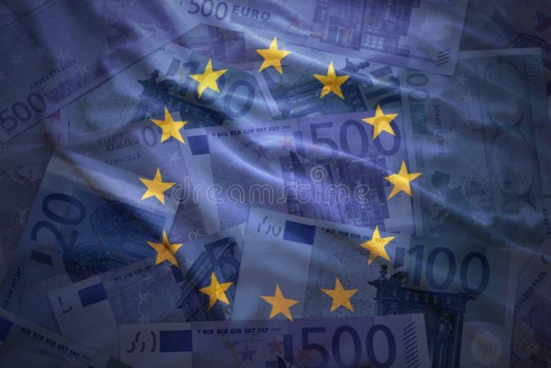 Bandiera di Unione Europea d'ondeggiamento variopinta su un euro fondo fotografia stock libera da diritti
