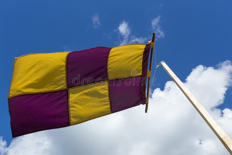 Bandiera gialla e porpora su un'insegna che ondeggia contro il vento sulla a fotografia stock libera da diritti