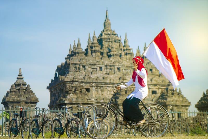 Bandiera indonesiana della falda di Hijab dell'asiatico nel bycycle, festa dell'indipendenza dell'Indonesia immagini stock libere da diritti