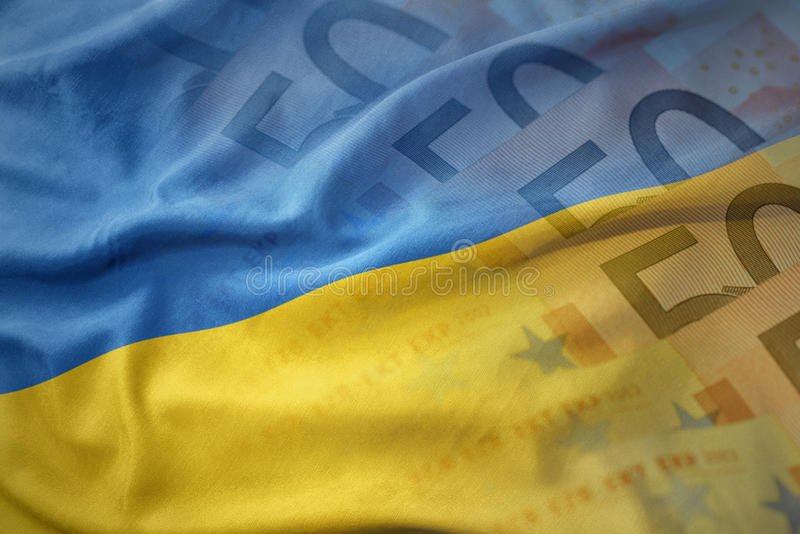 bandiera nazionale d'ondeggiamento variopinta dell'Ucraina su un fondo delle banconote dei soldi dell'euro fotografie stock libere da diritti