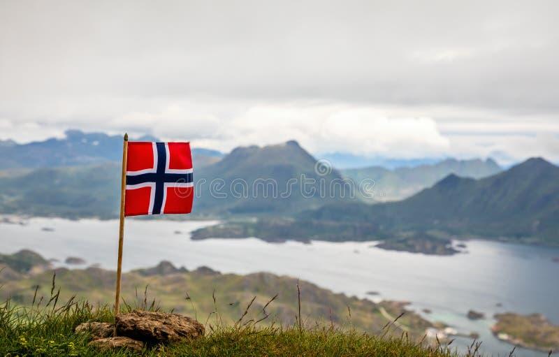 Bandiera nazionale norvegese nel vento sulla cima del picco di Nonstinden con il fiordo nei precedenti, Ballstad, comune di Vestv fotografia stock libera da diritti