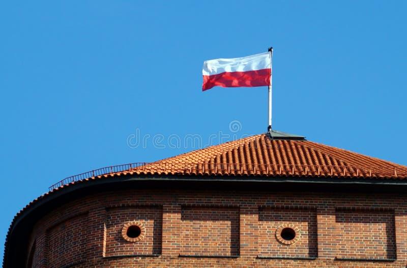 Bandiera nazionale polacca sulla cima della torre di Wawel del tetto fotografia stock libera da diritti