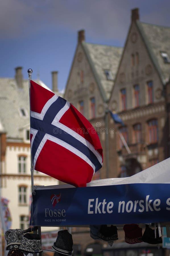 Bandiera norvegese con Bryggen dietro fotografia stock libera da diritti