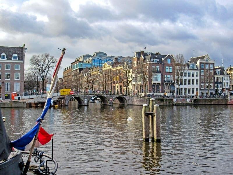 Bandiera olandese sulla barca con le costruzioni di mattone fiamminghe tradizionali del duch famoso di Amsterdam e del ponte immagine stock
