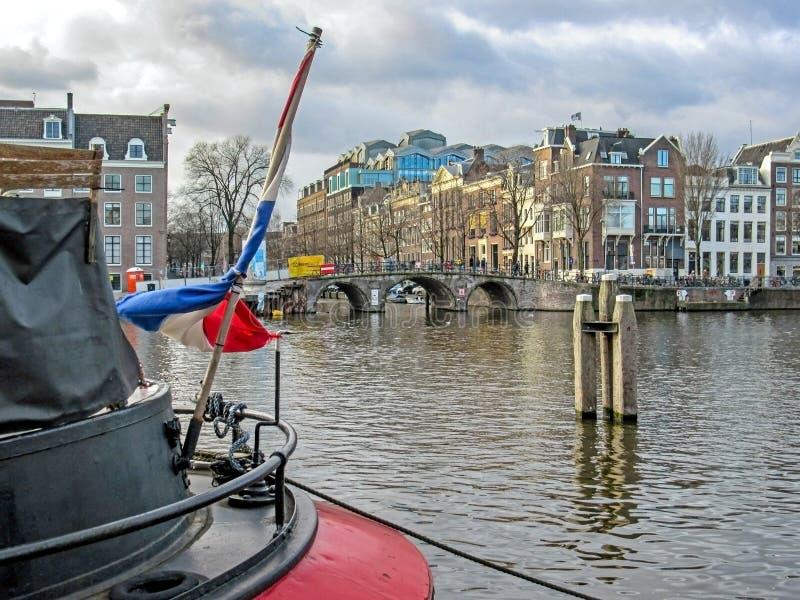 Bandiera olandese sulla barca con le costruzioni fiamminghe tradizionali olandesi famose di mattone di Amsterdam e del ponte fotografia stock